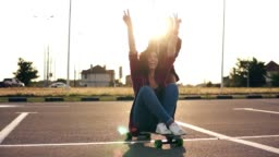 Cheerful woman sitting on a longboard and raising her hands up happily while her friend is pushing her behind during sunset. Lens flare. Slowmotion shot