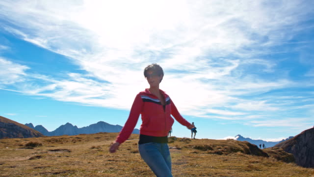 ws cheerful woman skipping in the mountains - julian alps stock videos and b-roll footage