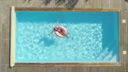 AERIAL, TOP DOWN: Cheerful woman sunbathing while relaxing in her backyard pool.