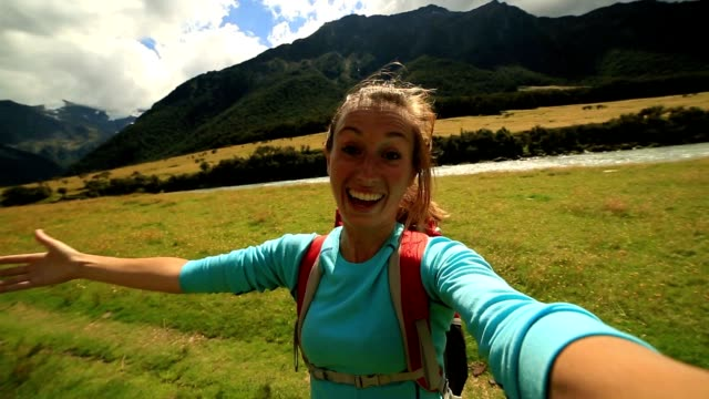 Cheerful woman takes a self portrait in mountain valley,