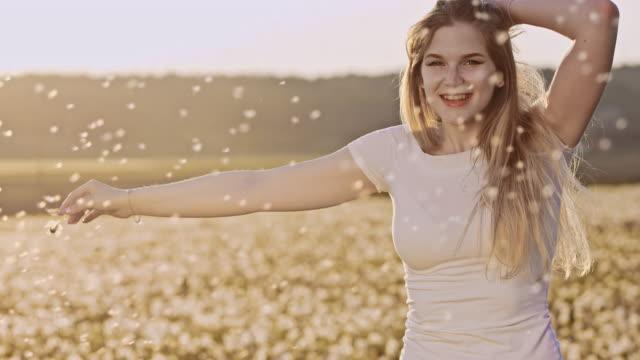 vídeos y material grabado en eventos de stock de en cámara lenta alegre mujer girando con semillas de diente de león - semilla