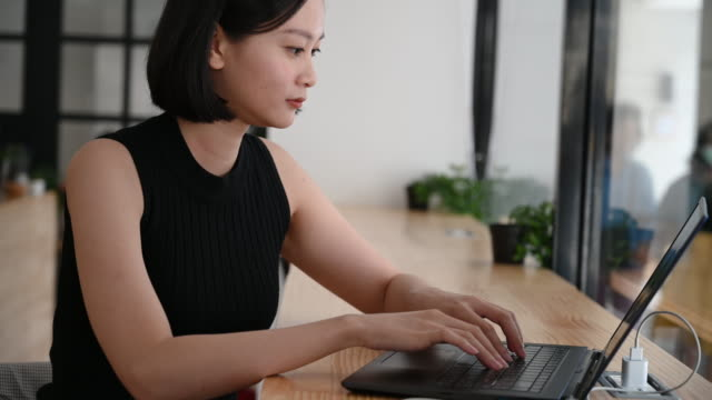 cheerful woman using laptop turning and smiling to camera - convenience stock videos & royalty-free footage