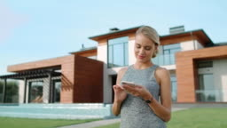 Cheerful woman using mobile phone at luxury apartment.