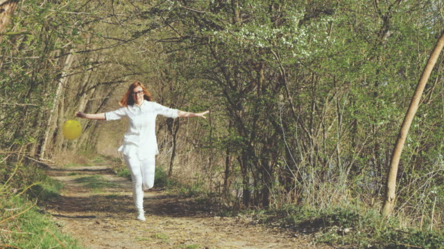 slo mo cheerful woman with a balloon skipping in the forest - skipping along stock videos & royalty-free footage