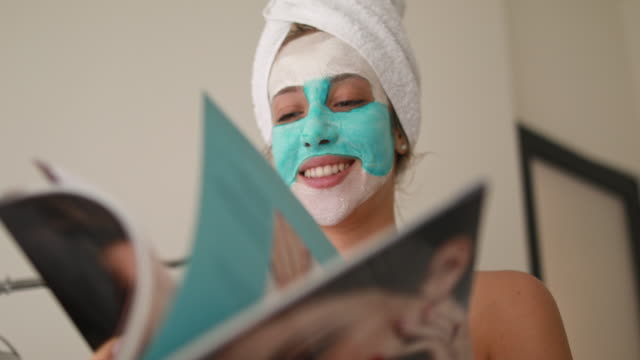 cheerful woman with a beauty mask reading a magazine at a spa - magazine publication stock videos & royalty-free footage
