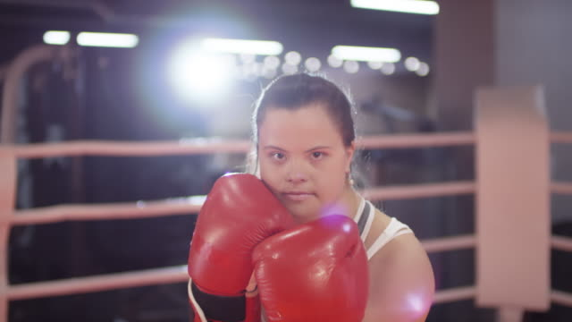 cheerful woman with down syndrome boxing on ring and posing for camera - persons with disabilities stock videos & royalty-free footage