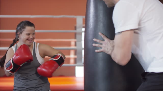 cheerful woman with down syndrome having boxing workout with trainer - boxing women's stock videos & royalty-free footage