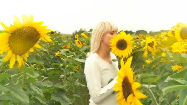 hd-zeitlupe: fröhliche frau mit sonnenblumen - menschliche gliedmaßen stock-videos und b-roll-filmmaterial