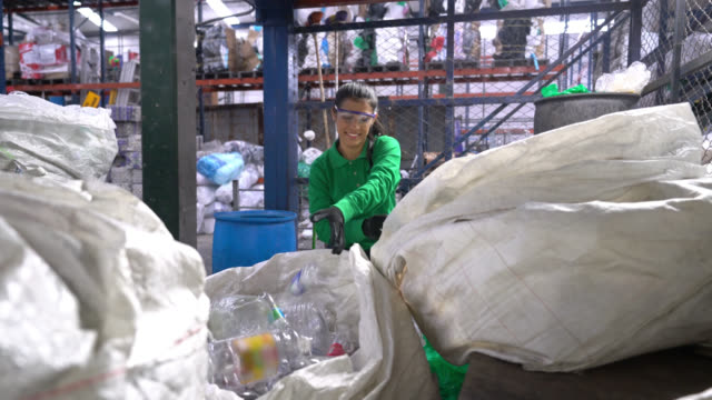 cheerful woman working at a recycling factory separating plastic bottles from a bag - environment stock videos & royalty-free footage