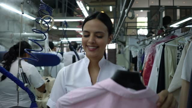 cheerful woman working at an industrial laundry service walking looking for a rail to hang a shirt - launderette stock videos & royalty-free footage