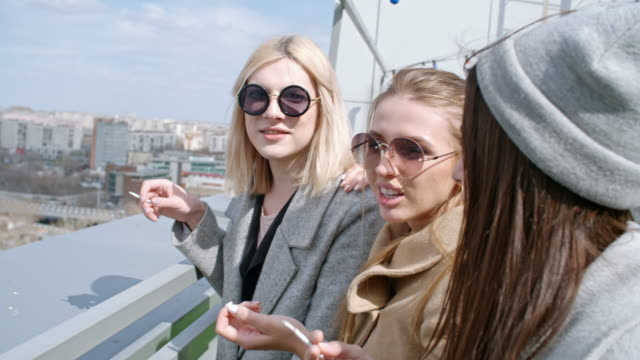 cheerful women and transgender person smoking on rooftop - smoking issues stock videos and b-roll footage