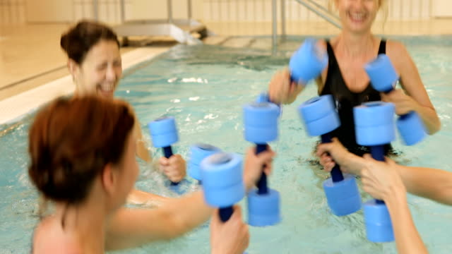 Cheerful women holding dumbbells in swimming pool