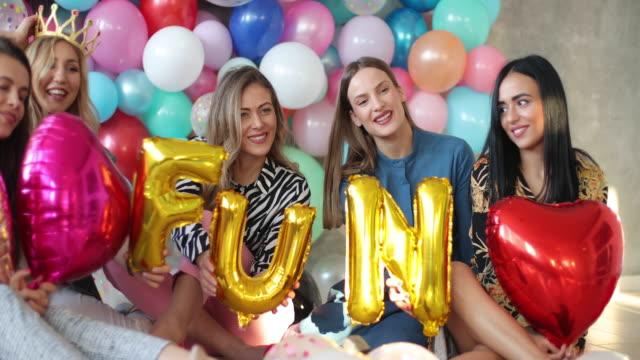 vídeos y material grabado en eventos de stock de mujeres alegres sosteniendo diversión escrita con globos de fiesta - globo de helio