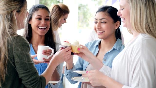 vídeos y material grabado en eventos de stock de las mujeres alegres 'tostar' cupcakes durante un evento de caridad - anfitriona de la fiesta