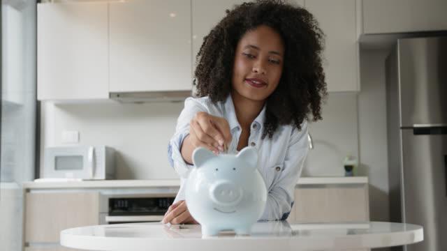 vidéos et rushes de jeune femme afro gaie à la maison insérant des pièces de monnaie dans la tirelire - tirelire