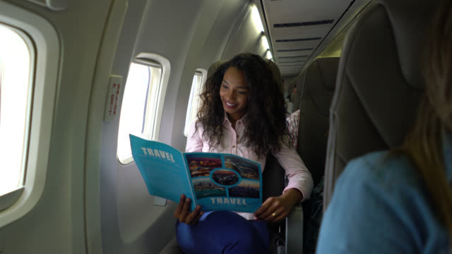 Cheerful young black woman looking at a travel guide while on flight