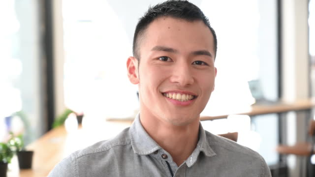 cheerful young businessman with toothy smile turning head - chinese ethnicity stock videos & royalty-free footage
