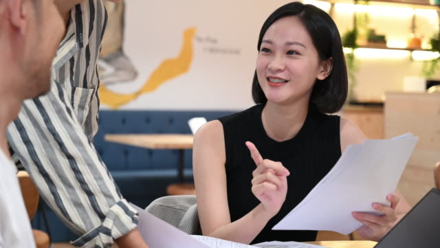 cheerful young businesswoman discussing with coworkers - solution stock videos & royalty-free footage