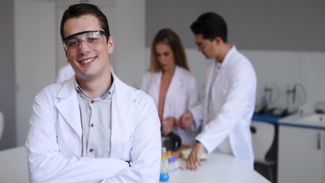 vídeos de stock, filmes e b-roll de alegre jovem químico em laboratório - braços cruzados