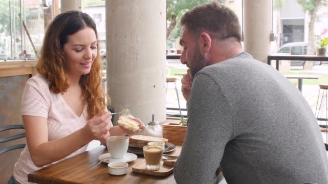 fröhliches junges paar, das tee in einer bäckerei trinkt, und mann, der ein brot mit der frau teilt, während er spricht - argentinien stock-videos und b-roll-filmmaterial