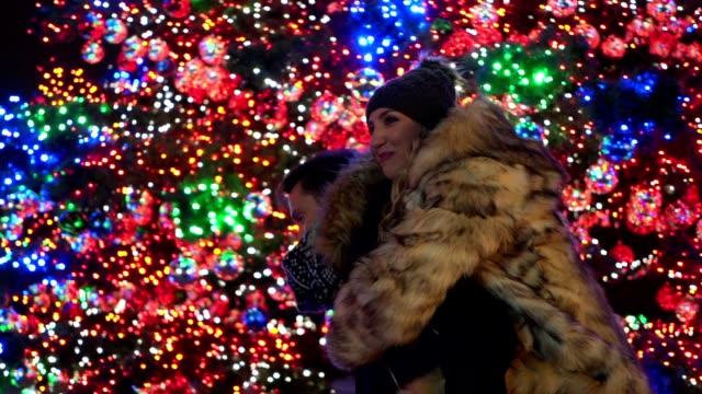 vídeos y material grabado en eventos de stock de alegre joven pareja disfrutando un piggyback junto a un árbol de navidad del centro de la ciudad - abrigo de invierno