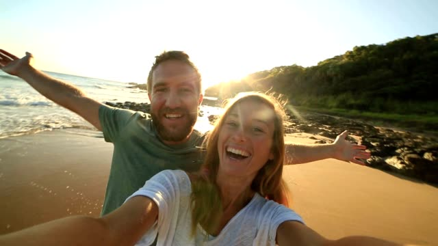 Cheerful young couple on the beach take a selfie portrait