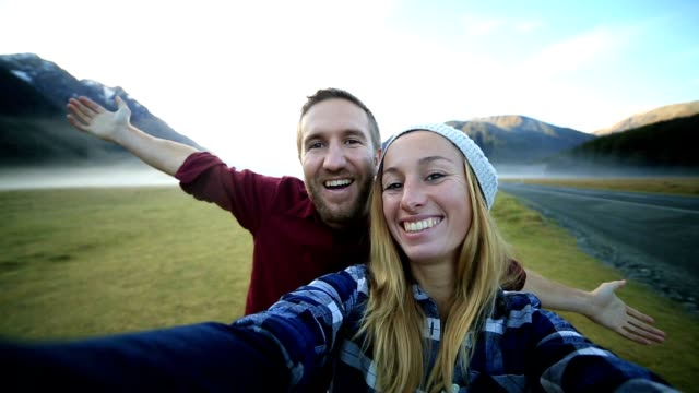 cheerful young couple take a selfie portrait by the road - things that go together stock videos & royalty-free footage