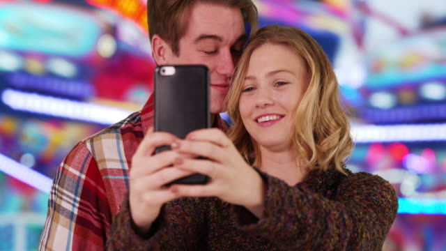 cheerful young couple taking a selfie at county fair, smiling and laughing - 遊園地点の映像素材/bロール