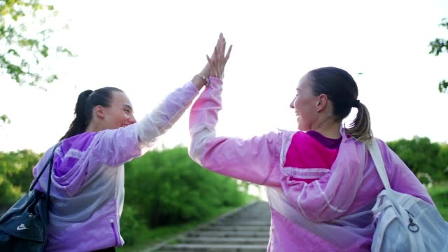 cheerful young female athletes returning from training carrying gym bags - motivation stock videos & royalty-free footage