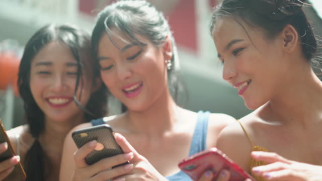 cheerful young friends looking at smart phone laughing - three people stock videos & royalty-free footage