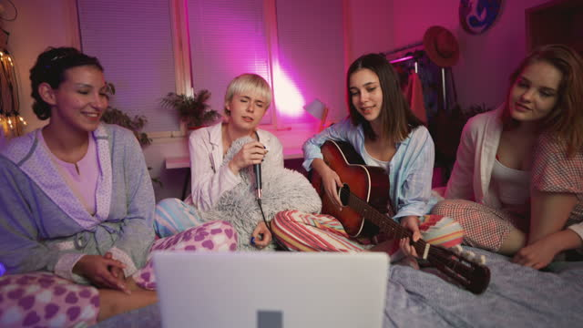cheerful young girlfriends singing karaoke at a slumber party - slumber party stock videos & royalty-free footage