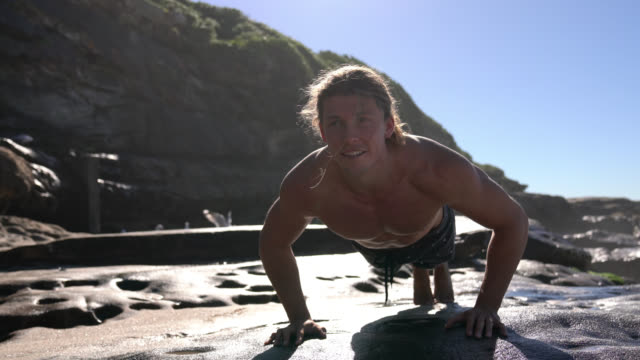cheerful young man exercising next to the ocean doing push ups - capelli biondi video stock e b–roll