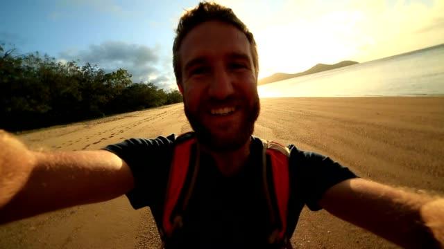 Vrolijke jongeman op het strand neemt een selfie-portret