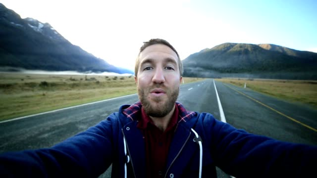 Cheerful young man takes a selfie portrait by the road