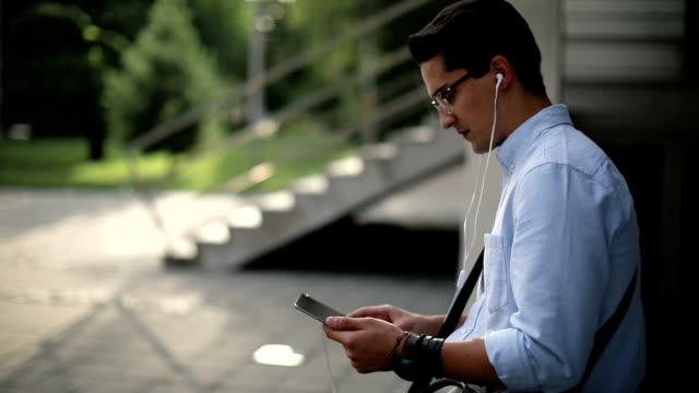 glad ung man använder surfplatta för online chat - ansvarsfullt företagande bildbanksvideor och videomaterial från bakom kulisserna