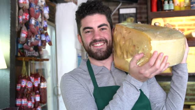 vídeos y material grabado en eventos de stock de joven alegre que trabaja en una tienda de delicatessen llevando un gran pedazo pesado de queso de rueda mientras sonríe a la cámara - tendero