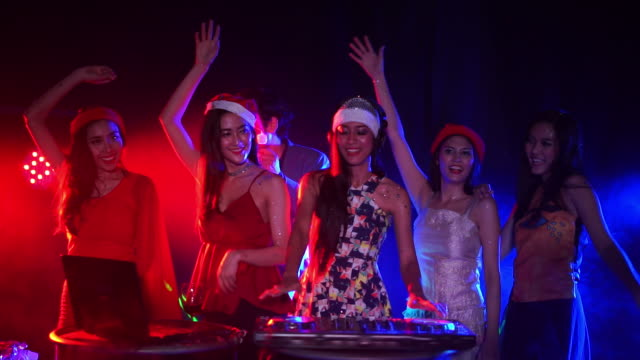 Cheerful young people dancing on night party, Dj mixed music at night club. New Year's Party 2018 concept.