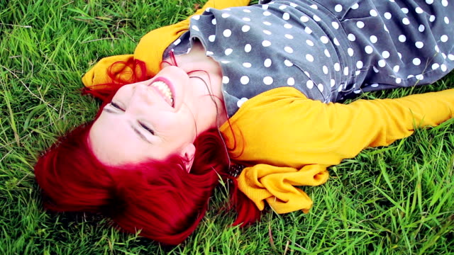 Cheerful young red haired woman relaxing in grassy meadow
