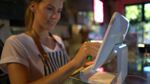 vídeos y material grabado en eventos de stock de camarera joven alegre registrar un orden en el sistema buscando muy feliz en una panadería - propietario