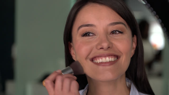 cheerful young woman applying powder with a make up brush looking at the mirror - applying stock videos & royalty-free footage