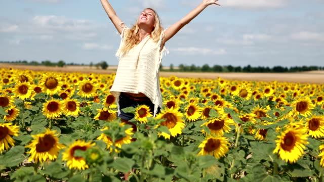 Fröhliche junge Frau Ausgestreckte Arme in der Mitte von Sonnenblumen-Feld