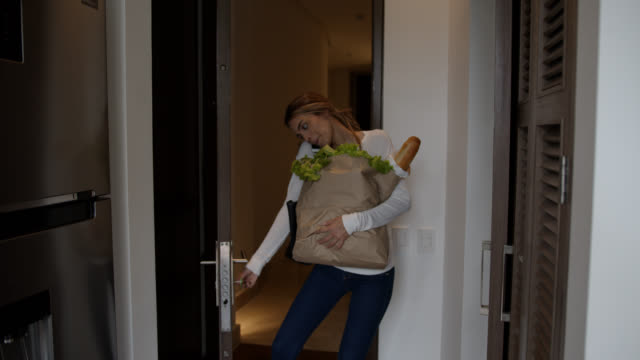 vídeos de stock e filmes b-roll de cheerful young woman arriving home carrying groceries talking on the phone and opening the door - saco objeto manufaturado