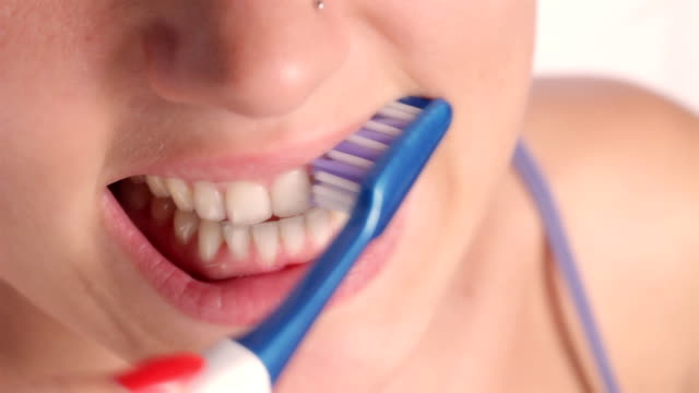 cheerful young woman brushing teeth. - toothbrush stock videos & royalty-free footage