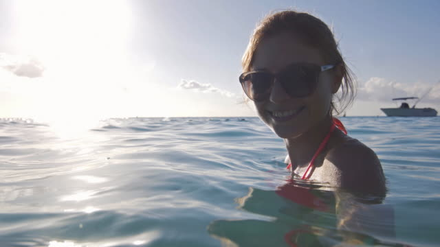 cheerful young woman feeling relaxed in the ocean - city break stock videos and b-roll footage