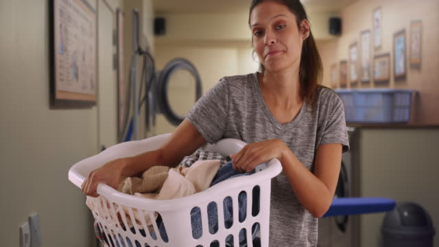 vidéos et rushes de cheerful young woman holding basket of clothes in laundry room - lessive produit d'entretien