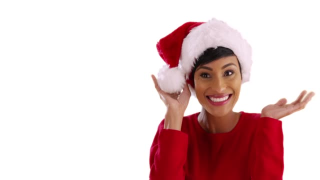 cheerful young woman modeling santa claus hat, smiling and laughing in studio - santa hat stock videos & royalty-free footage