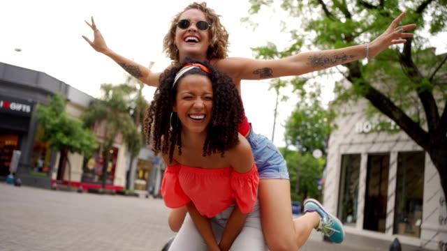 ピギーバックに乗って陽気な若い女性 - おんぶ点の映像素材/bロール