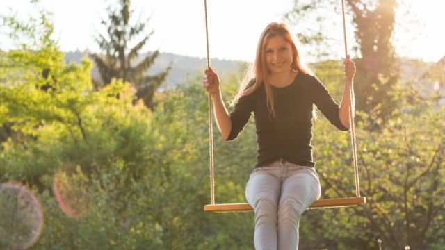 cheerful young woman on rope swing in backyard at sunrise - legs crossed at ankle stock videos & royalty-free footage