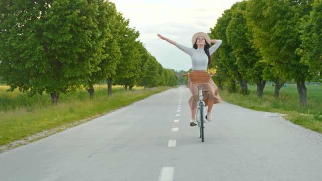 slow motion cheerful young woman riding a bike - treelined stock videos & royalty-free footage
