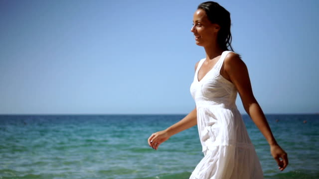 cheerful, young woman running on the beach - one young woman only stock videos & royalty-free footage